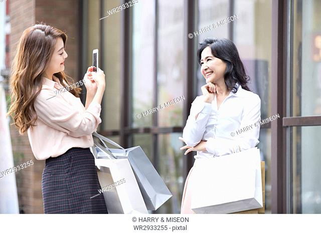 Smiling mother and daughter with shopping bags posing for photo