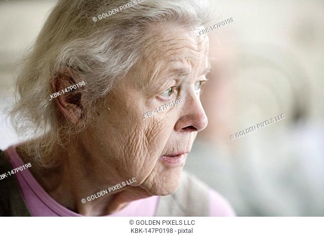 Close-up of a stoic and pensive senior woman staring into space