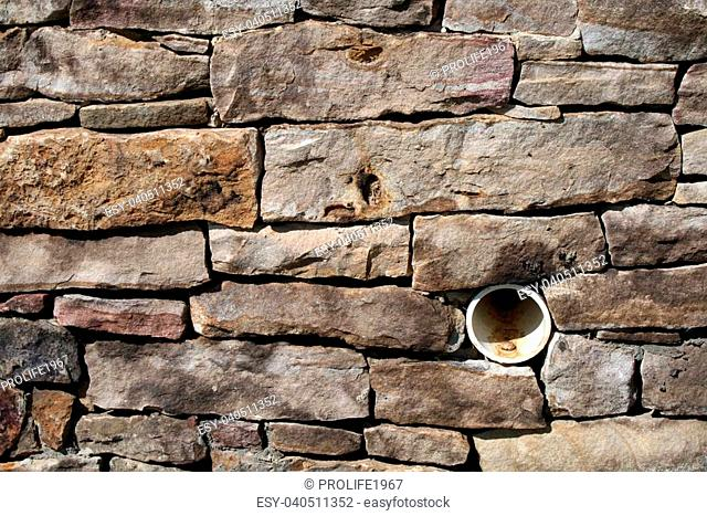 A beautiful and colourful stone,brick wall is used to disguise the drainage pipe intended to keep rainwater from flooding nearby buildings