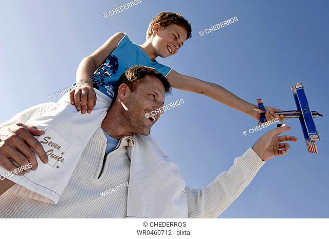 Low angle view of a mid adult man carrying his son on his shoulders and laughing