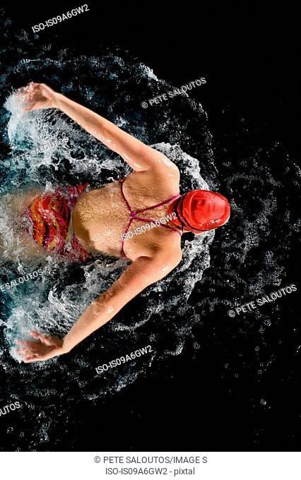 Teenage girl doing butterfly stroke in swimming pool