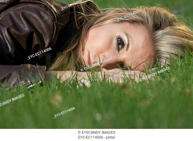 Mid adult woman relaxing on grass