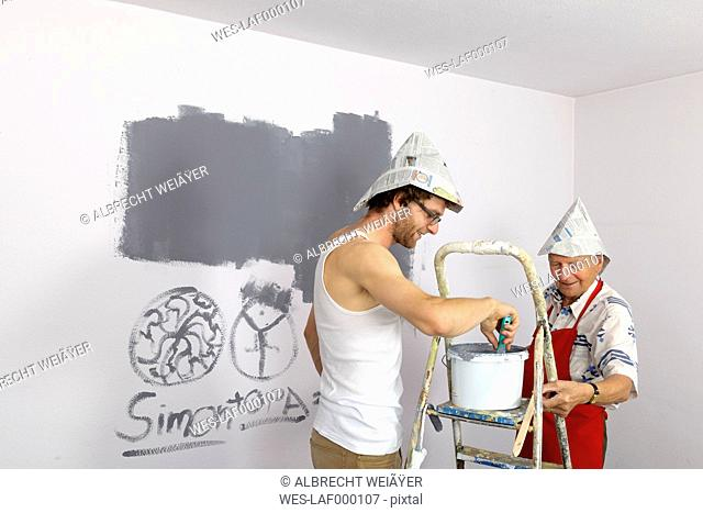Germany, Grandfather and grandson painting wall
