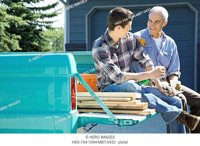 Father and son sitting on tailgate taking a break