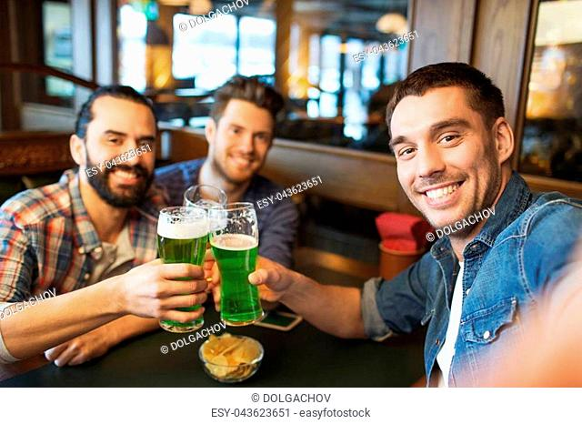 leisure, friendship, st patricks day and celebration concept - happy male friends drinking green beer and taking selfie at bar or pub