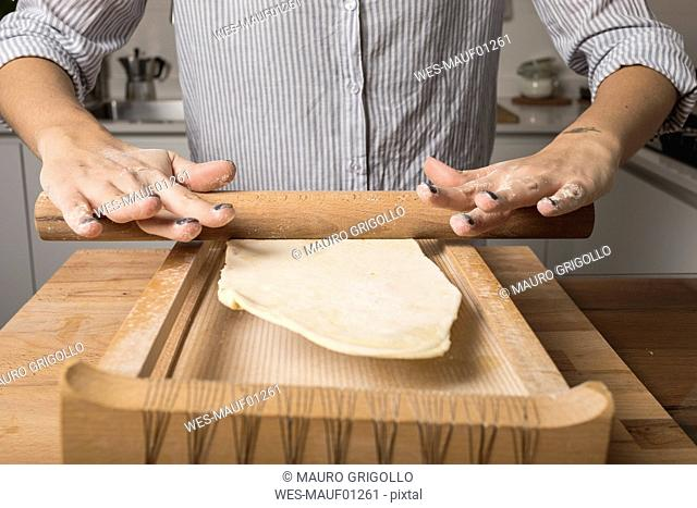 Woman preparing pasta, rolling out the noodle dough with rolling pin, pasta harp