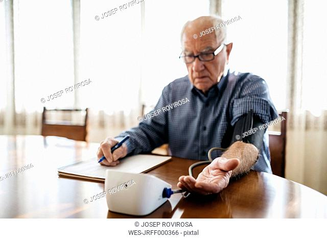 Senior man controlling his blood pressure at home