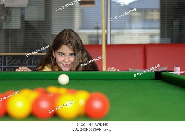 Young girl playing pool