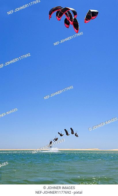 Men kite surfing over sea
