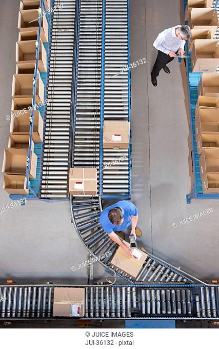 Workers packing boxes on conveyor belts in distribution warehouse