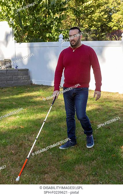 Man with visual impairment using his cane outdoors
