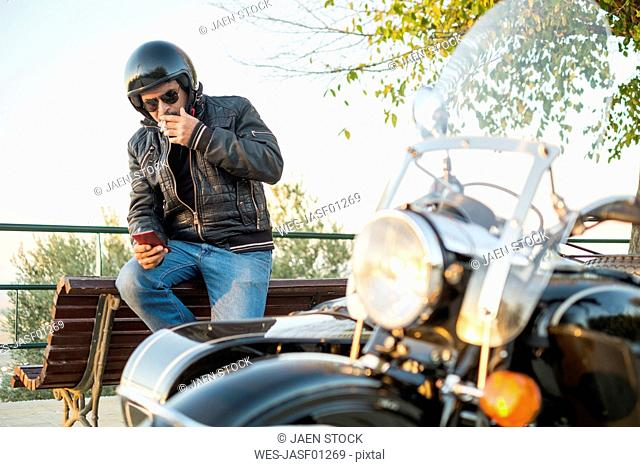 Biker wearing helmet and sunglasses having a cigarette rest looking at smartphone