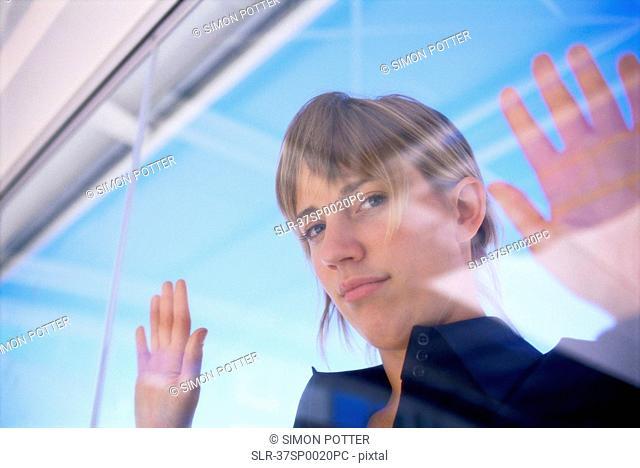 Woman peering in through glass window