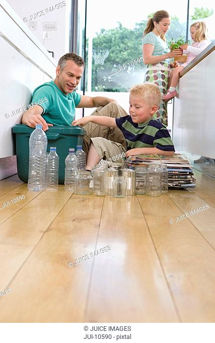 Family of four in kitchen, father and son 2-4 putting recycling into bin, low angle view