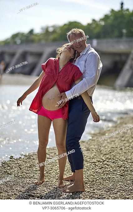 Couple, pregnancy, age difference, love, freedom. At river Isar, Munich, Germany