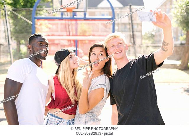 Four adult friends posing for smartphone selfie on basketball court