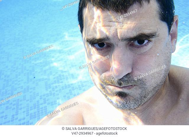 Man holding his breath under water in a pool