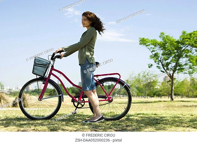 Young woman walking with bicycle in park