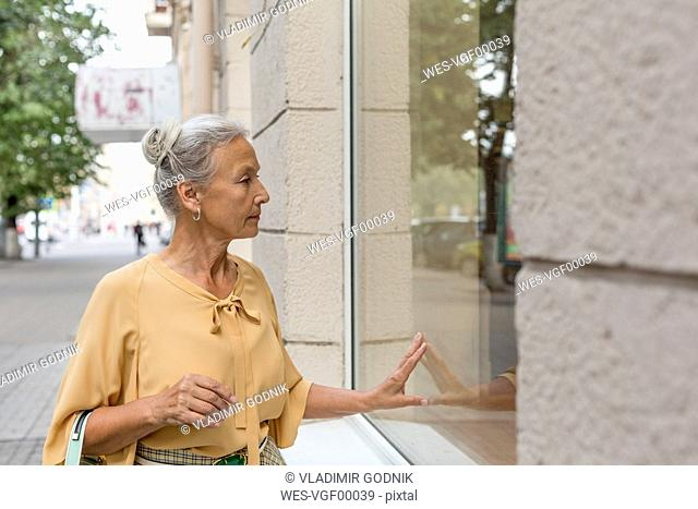 Senior woman looking in shop window