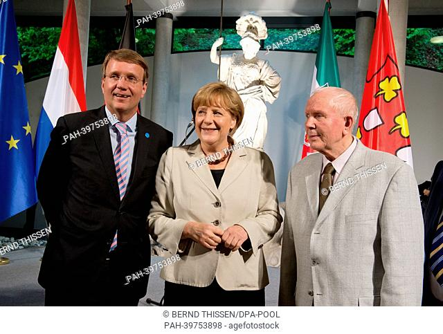 German Chancellor Angela Merkel (C) stands with Chancellery Minister Ronald Pofalla (L) and his father (R)during a reception for first German-DutchCabinet...