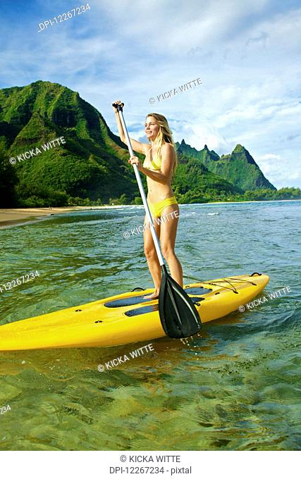 Young woman stand up paddle boarding; Kauai, Hawaii, United States of America