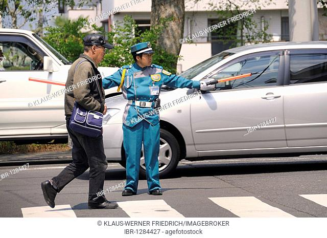 Typical police officer directing traffic in a parking lot, Kyoto, Japan, East Asia, Asia