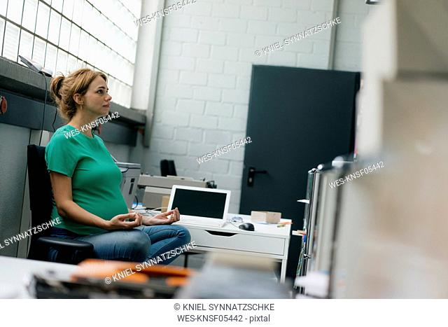 Pregnant woman sitting at desk in office having a yoga break