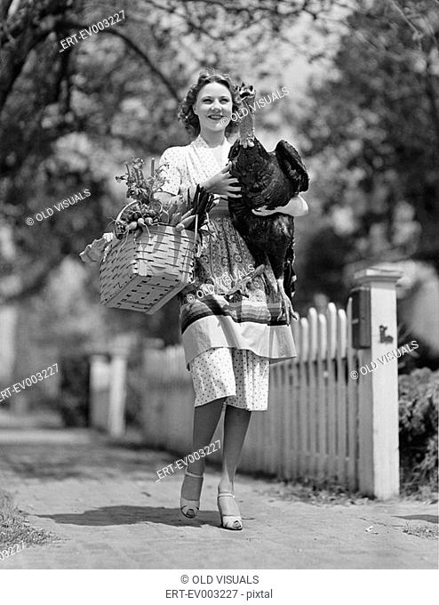 Woman carrying live turkey and grocery basket All persons depicted are not longer living and no estate exists Supplier warranties that there will be no model...