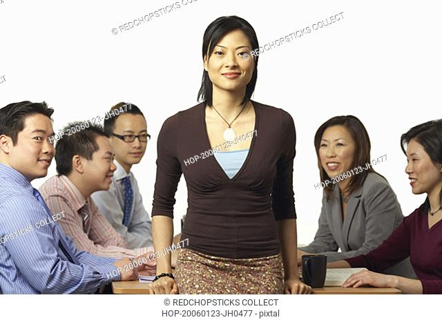 Portrait of a businesswoman leaning against a table with business executives sitting behind her
