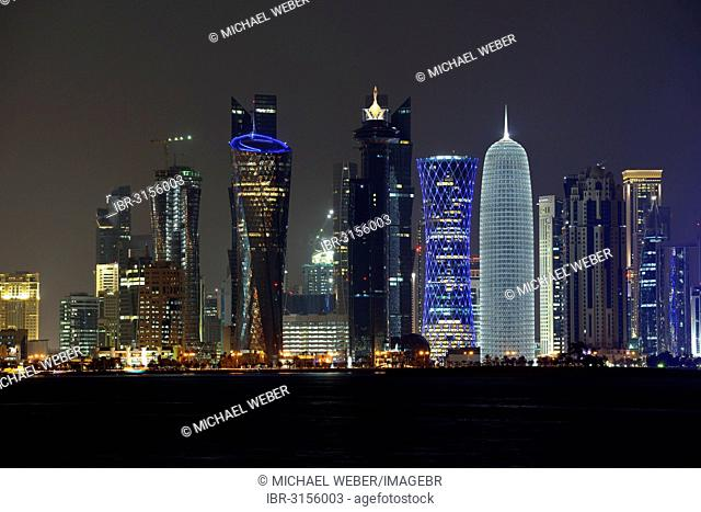 Skyline of Doha at night with the Al Bidda Tower, Palm Tower 1 and 2, the World Trade Center, Tornado Tower and the Burj Qatar Tower with silver illuminations