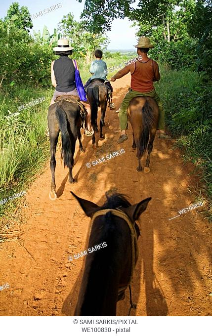 Family horseback riding in the countryside along with their Cuban guide, Vinales valley, Cuba