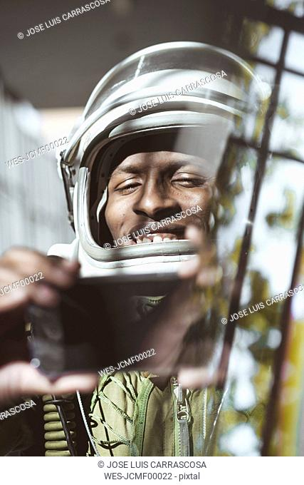 Happy astronaut in spacesuit using smartphone