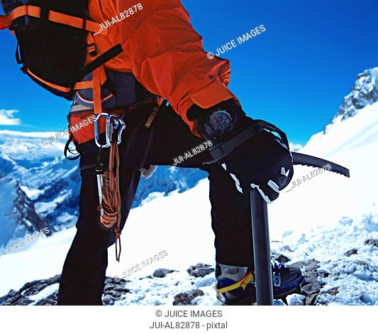 Close up of hiker holding ice axe on snowy mountain