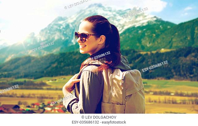 travel, tourism and people concept - happy young woman with backpack over alps mountains background