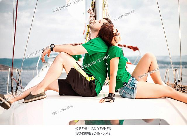Couple sitting back to back on sailboat