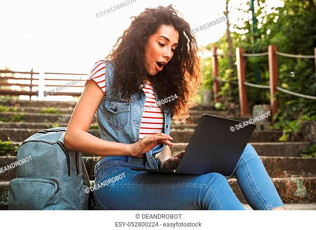 Photo of excited brunette woman sitting on stairs in park on summer day and using silver laptop with surprise