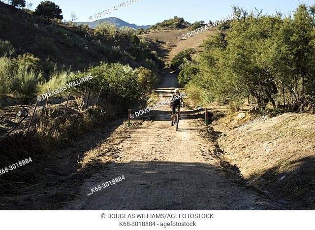 A woman, 70, cycles on the Via verde de la Sierra, Cadiz, Spain, bicycling route