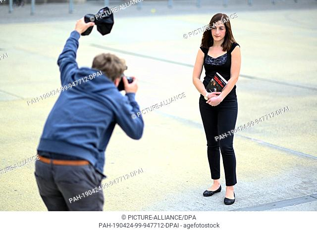 "24 April 2019, Baden-Wuerttemberg, Ulm: The journalist Mesale Tolu holds her book """"My son stays with me"""" in her hand while a photographer photographs her"
