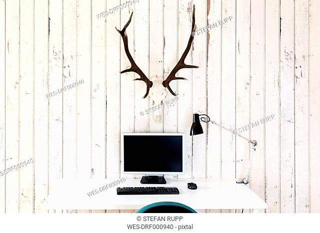 Home office with personal computer and deer antler hanging on wooden wall