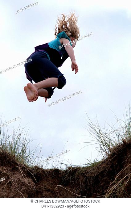 child girl jumping from sand dune