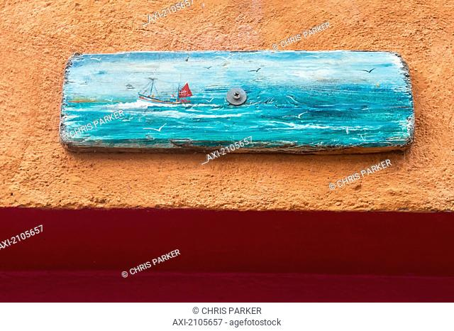 United Kingdom, England, Cornwall, Driftwood Painting Of Fishing Boat Above Entrance To Seafood Restaurant; Falmouth