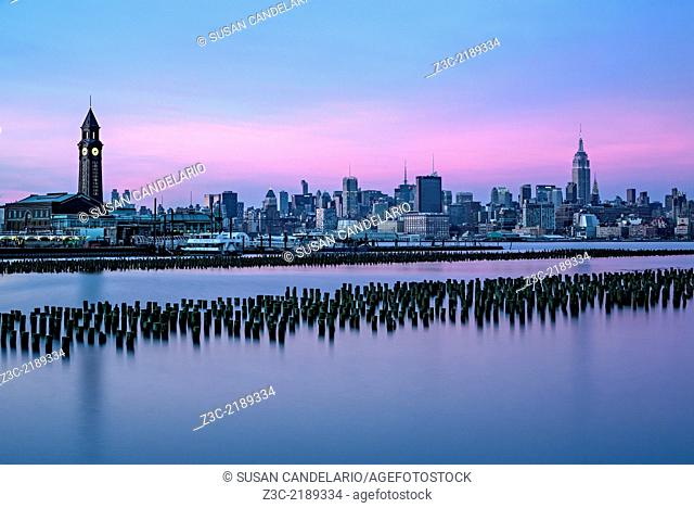 The New York City skyline along with Empire State Building illuminated in pastel colors and the Erie Lackawanna Terminal in Hoboken