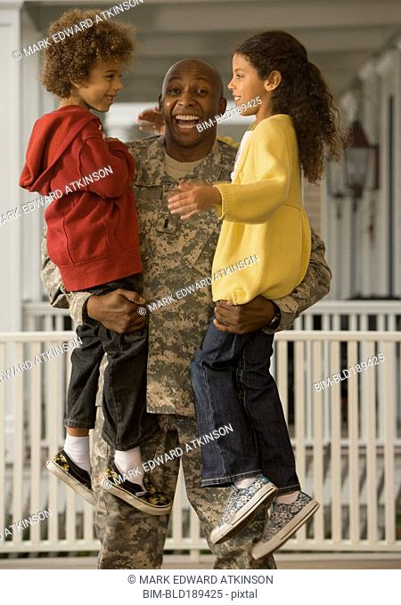 African soldier holding son and daughter