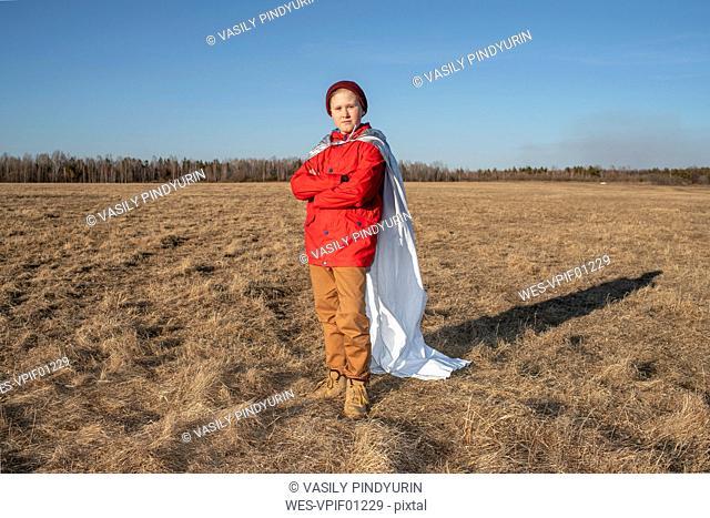 Boy dressed up as superhero posing in steppe landscape