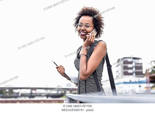 Smiling businesswoman telephoning with cell phone