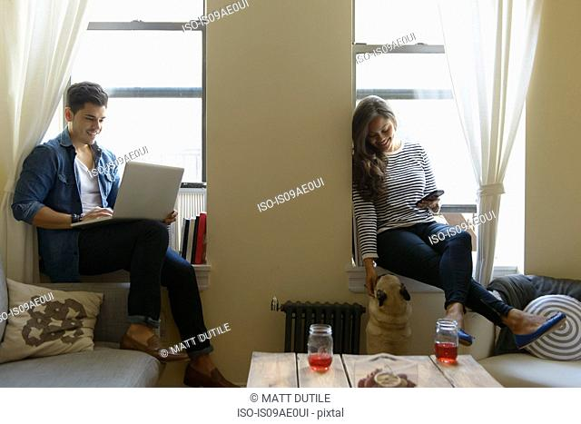 Young couple sitting on window sill using laptop and smartphone