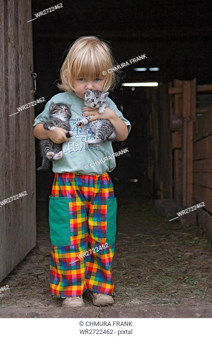 blond boy holding two kittens at the stable door