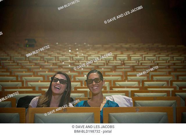 Hispanic women watching 3-D movie in theater