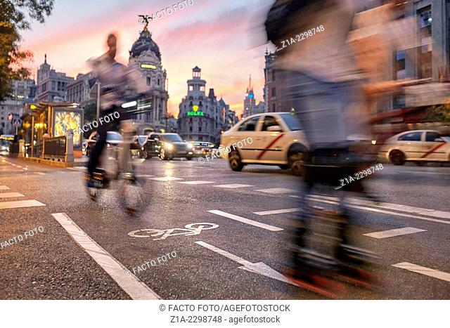 Cyclist and skater at the cycle lane of Alcala street with Gran Via street at the background. Madrid, Spain