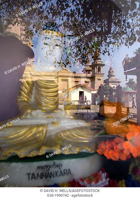 Buddha statue and reflection of historic temple in Varanasi, Uttar Pradesh, India